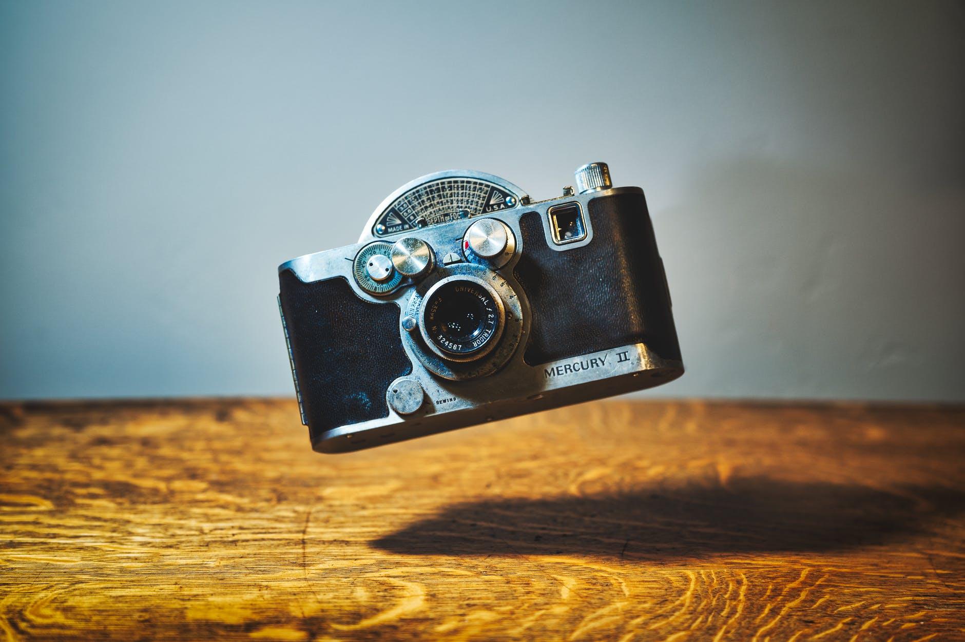 retro photo camera above wooden table